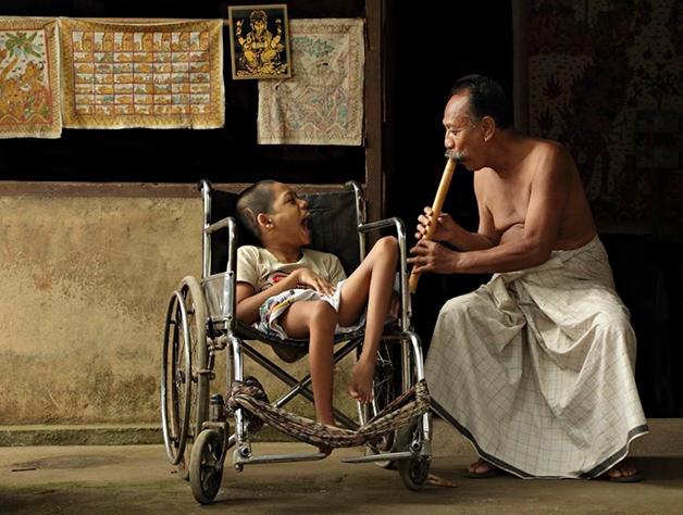 Homem conforta crianca com deficiencia atraves da musica